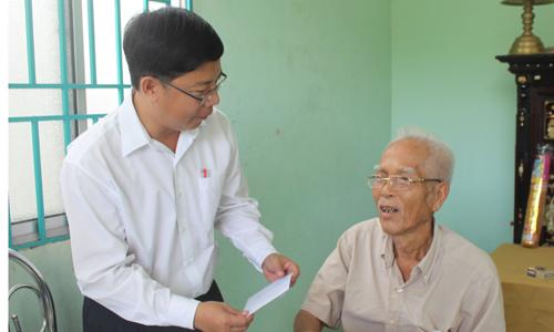 Bí thư Huyện ủy Cái Bè Trần Thanh Nguyên tặng quà cho ông Nguyễn Văn Thuần (thương binh 71%), ngụ ấp Hòa.