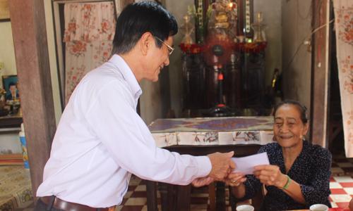 Gi ám đốc Sở Lao động, Thương binh và Xã hội tỉnh Tiền Giang Phạm Minh Trí tặng quà cho bà Lê Thị Sáu (vợ liệt sĩ), ngụ ấp Hòa.