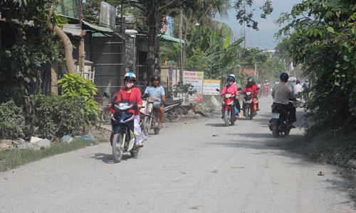 Người dân lưu thông trên huyện lộ 62 (xã Long Trung,  huyện Cai Lậy) phải chịu cảnh bụi tung mịt mù.