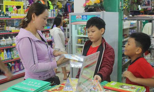 Phụ huynh dẫn con, cháu đi mua sắm đồ dùng học tập chuẩn bị cho năm học mới.