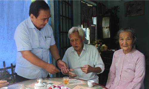 Phó Bí thư Thường trực Tỉnh ủy Võ Văn Bình trao quà cho ông Phạm Văn Ba (thương binh 61%), ngụ ấp Hòa, xã Hòa Hưng.