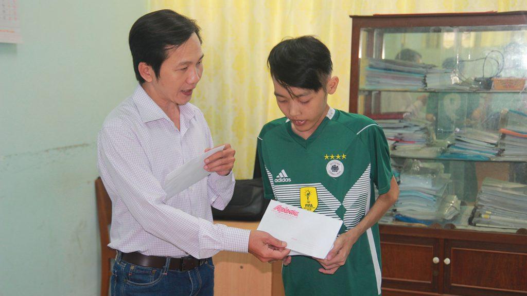Phó Tổng Biên tập Báo Ấp Bắc Nguyễn Trọng Tấn trao tiền của bạn đọc giúp đỡ em Nguyễn Phan Quí.