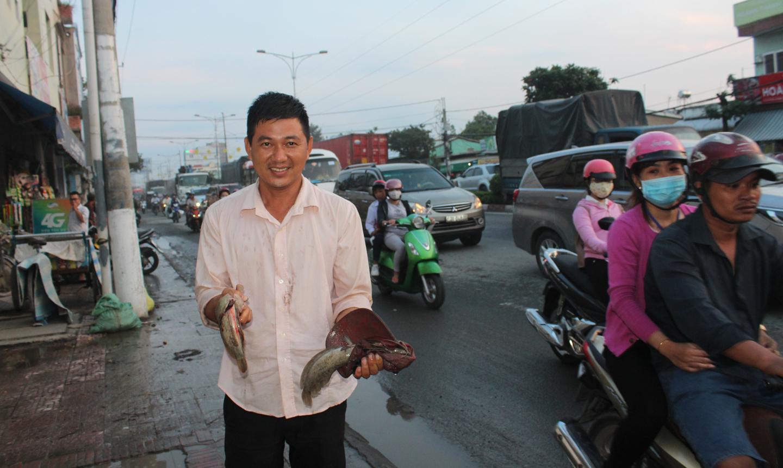 Người dân bắt được cá do triều cường ngập.