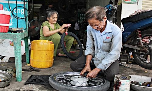 """""""Thợ phụ"""" ở tiệm sửa xe của ông Long là bà Võ Thị Lệ, 60 tuổi. Bà cho biết, bà yêu và chấp nhận """"góp gạo thổi cơm chung"""" với chàng trai sửa xe năm ấy bởi đức tính hiền lành, chất phát và sống lương thiện với nghề, với đời."""