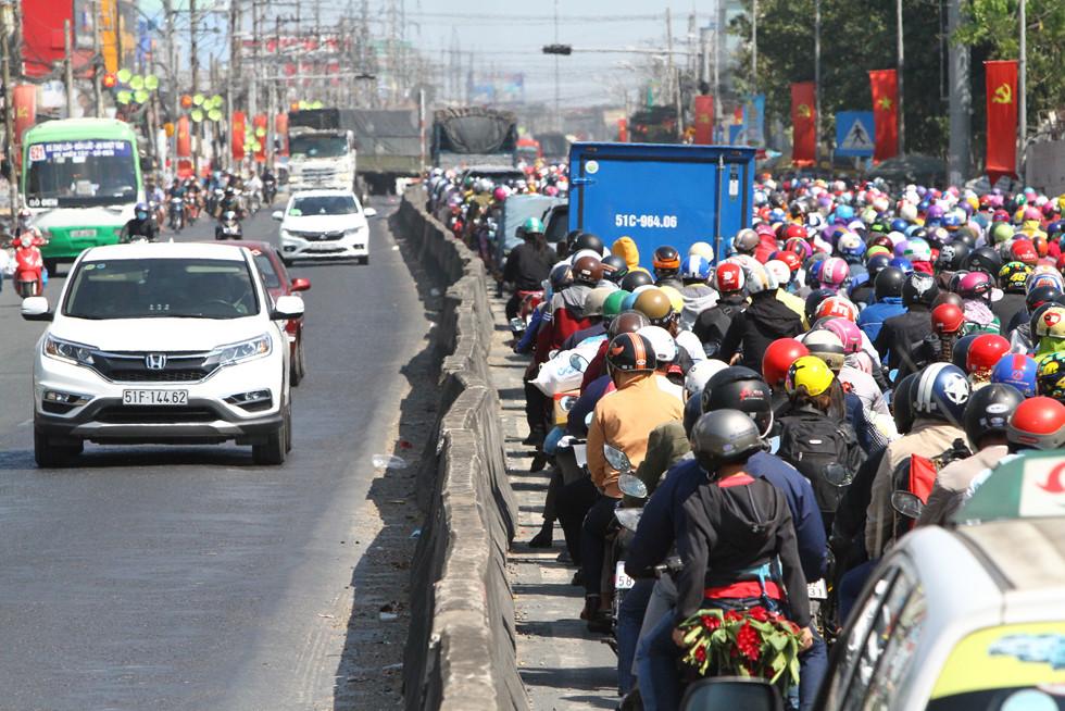 Dòng người miền Tây về lại Sài Gòn làm việc sau Tết ken cứng trên QL 1A - ảnh 16