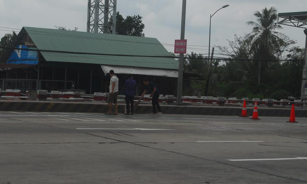 Nhân viên công ty vệ sinh gần Trạm Thu phí BOT Cai Lậy.