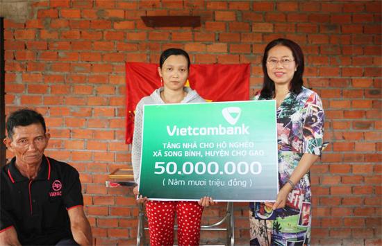 Bà Nguyễn Thị Tuyết, Giám đốc Vietcombank Tiền Giang trao biển biểu trưng cho gia đình bà Diễm.