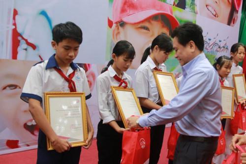 Ông Trần Văn Dũng - Phó Chủ tịch UBND tỉnh Tiền Giang trao quà cho các em HS.