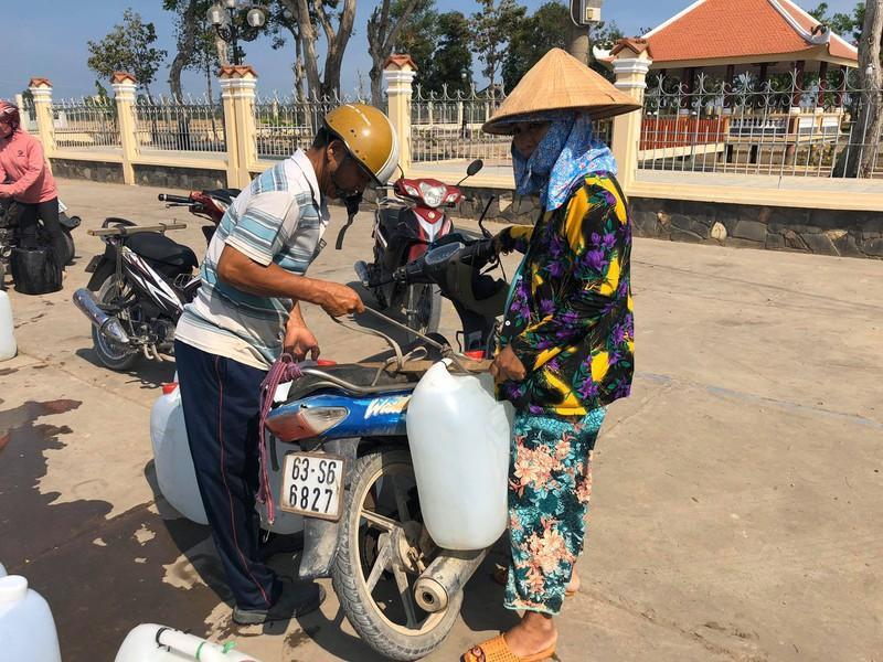 Các hộ dân giúp đỡ lẫn nhau để đưa nước về nhà.
