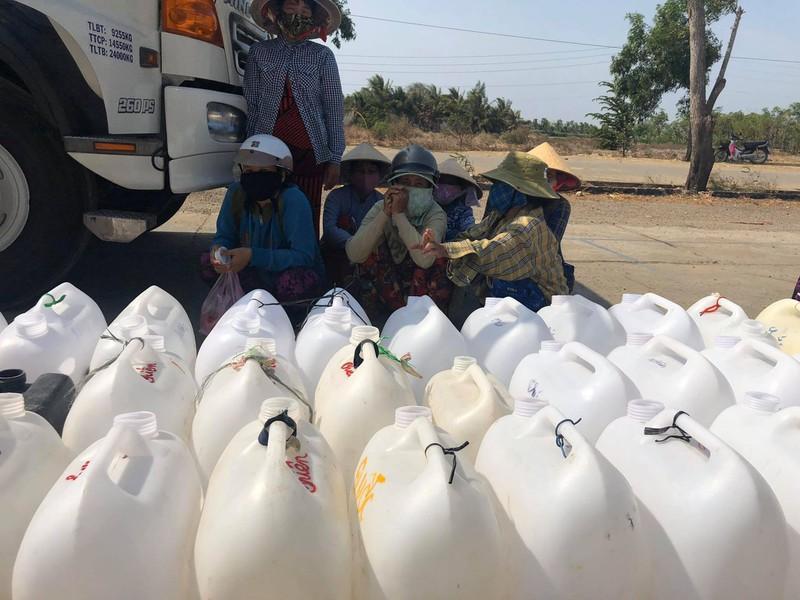 Người dân vừa lấy nước vừa trốn nắng.