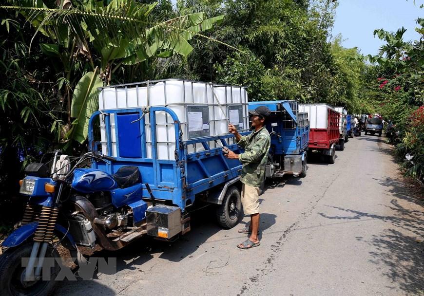 Người dân trên địa bàn xã Thanh Hòa, thị xã Cai Lậy đến lấy nước ngọt miễn phí tại điểm cung cấp nước ngọt cầu Ông Thiệm. (Ảnh: Vũ Sinh/TTXVN)