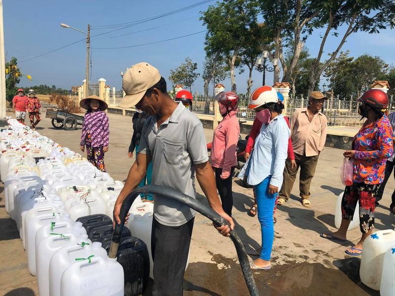 Hàng trăm can nước xếp hàng để được lấy nước ngọt.