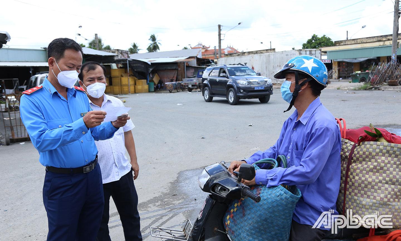 Kiểm tra giấy test thương lái ra vào Chợ Vĩnh Kim.