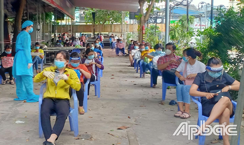 Sinh viên Nguyễn Thái An hỗ trợ công tác thu thập và lấy mẫu xét nghiệm test nhanh Covid-19.  Ảnh: Lê Tân