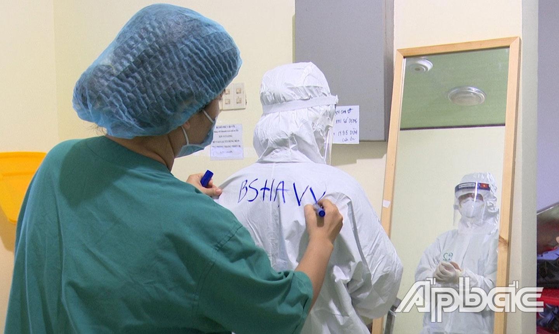Bác sĩ Hạ Vy chuẩn bị đồ bảo hộ trước khi vào điều trị cho bệnh nhân ở Trung tâm Hồi sức bệnh nhân Covid-19. Ảnh: Văn Thảo